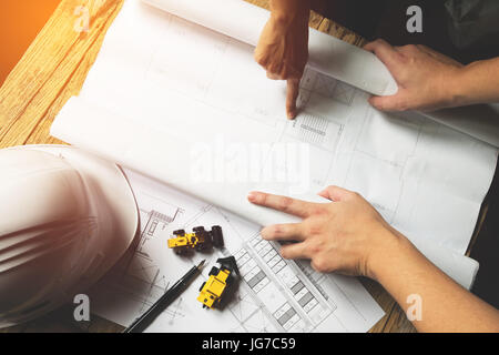 Creative architect projecting on the big drawings in the dark loft office with dark and retro style - Stock Photo