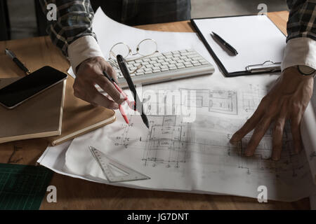 Creative architect projecting on the big drawings in the dark loft office or cafe with dark and retro style. - Stock Photo