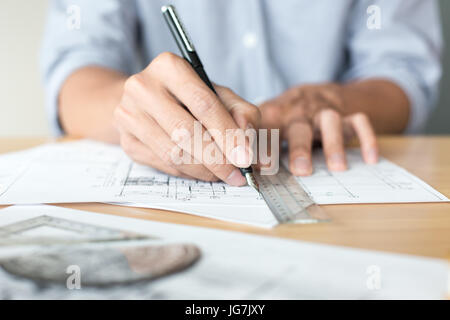 Creative architect projecting on the big drawings in the dark loft office or cafe with dark and retro style - Stock Photo