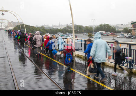 Southport, Merseyside. UK Weather. 4th July, 2017. Heavy rain arrives at the resort as school children enjoy a day - Stock Photo