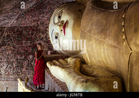 Buddhist novice monk / little monk / young monk worship big beautiful reclining  Buddha statue in Phowintaung cave - Stock Photo