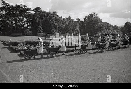 1940, England, Essex, group of nurses and chrome wheeled prams in the grounds of Stanstead Hall, home of Sydney - Stock Photo