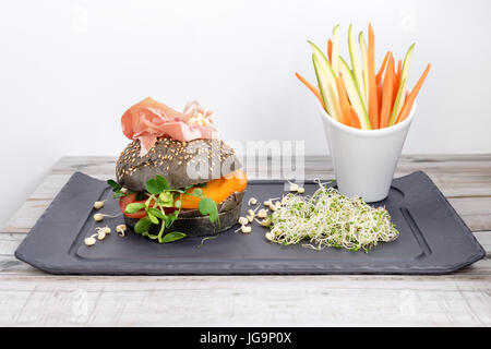 Healthy burger with hamon, tomatoes, micro greens and black wholegrain buns, vegetable sticks on black slate board - Stock Photo