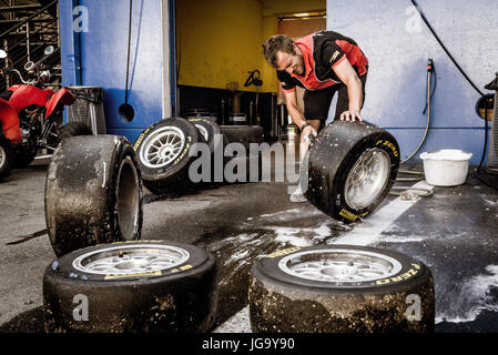 Mechanic working in circuit pit cleaning and washing racing tires set - Stock Photo