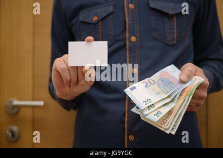 Businessman holding a bank card, and in the other hand holding the money in cash, finance, businessman - Stock Photo
