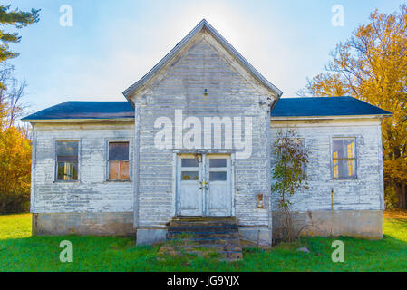 An old white abandoned farm house in the fall - Stock Photo