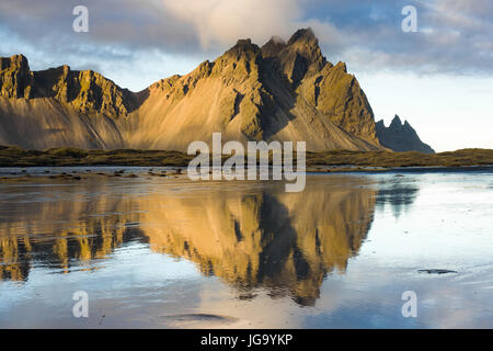Stokksnes and Vestrahorn mountains in late afternoon light reflected in shallow water, Iceland - Stock Photo