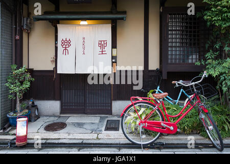 Old bicycle parking on a footpath in front of the house in by the street in a city of Japan - Stock Photo