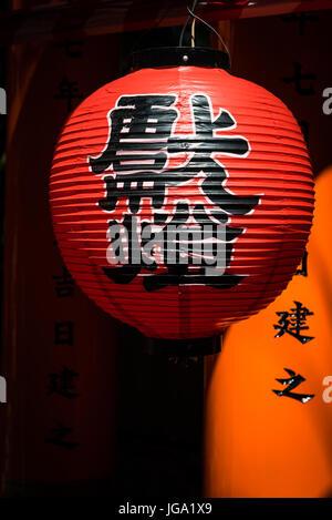 Red lantern hanging in  Fushimi Inari torii gates in Kyoto,  Japan - Stock Photo