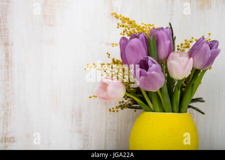 Bouquet Of Tulips And Mimosa In A Yellow Vase On A Wooden Background