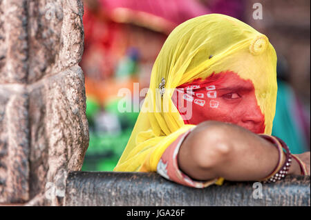 Young beautiful Indian girl waiting for the bus in traditional colored clothes, sari - Stock Photo