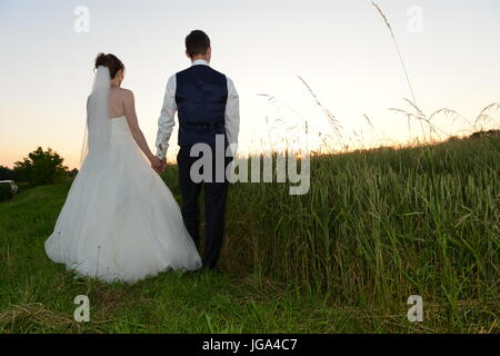 Young couple from the back standing in a field and watching sunset - Stock Photo