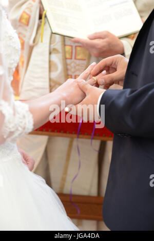 Bride an groom are exchanging their wedding rings in church, priest holding wedding book - Stock Photo