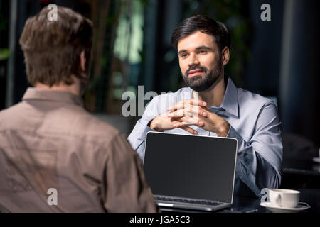 business team on meeting discussing project with laptop in cafe, business lunch concept - Stock Photo
