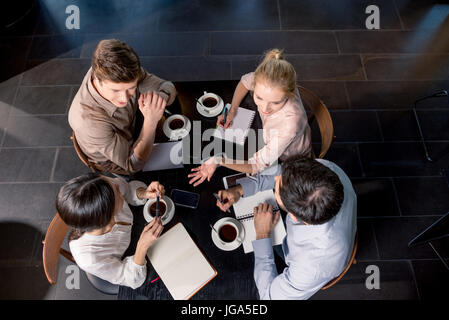Overhead view of young businesspeople discussing project at table with cups of coffee, business lunch concept - Stock Photo