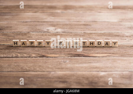 Alphabet letters on wooden pieces collected to word happy birthday - Stock Photo