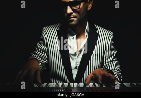 Musician on his instrument, keyboard player in stripped jacket, playing synth. - Stock Photo