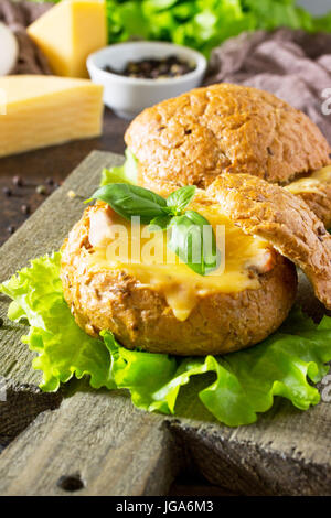 Delicious baked burger from bacon, eggs, cheese served with fresh lettuce leaves. Ingredients for cooking scrambled - Stock Photo