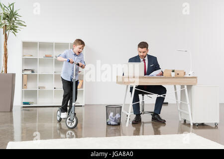 Happy boy riding skooter while his father businessman working at office - Stock Photo