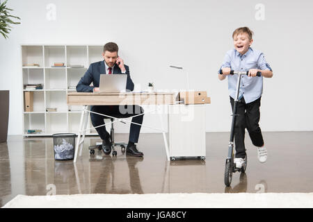 Happy boy riding skooter while his father working at office - Stock Photo