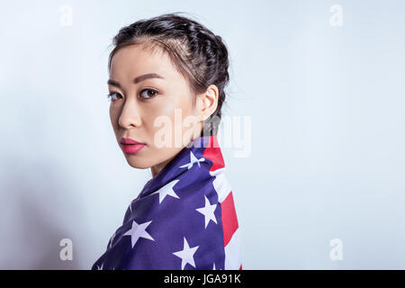 Portrait of stylish asian girl wrapped in american flag looking at camera isolated on grey - Stock Photo