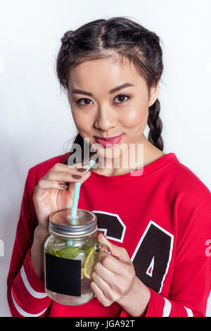 Attractive young asian woman drinking cold beverage and looking at camera isolated on white - Stock Photo