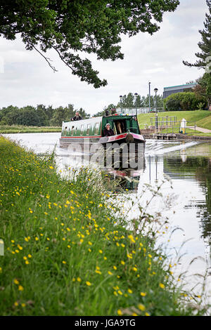 Narrow boat with two people on board travelling along Bridgewater Canal near to Daresbury International Science - Stock Photo