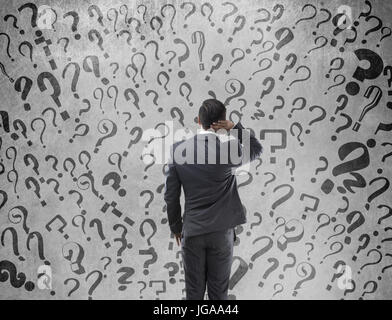 Rear view of confused businessman with question marks on wall - Stock Photo