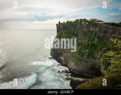 Sunset landscape with cliff and sea at Uluwatu temple in Bali island, Indonesia. Uluwatu is the number four surf - Stock Photo