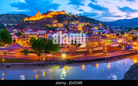 The twilight sky over the old Tbilisi, the bright lights of Narikala fortress and Old Town neighborhood are reflected - Stock Photo