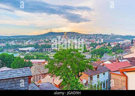 The scenic sunset sky over the old town of Tbilisi with the golden dome of Sameba Cathedral on the distance, Georgia. - Stock Photo