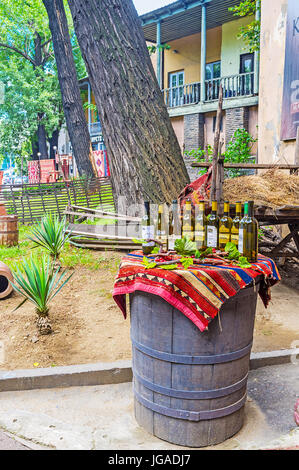 TBILISI, GEORGIA - JUNE 6, 2016: The barrel with wine bottles is the best commercial for traditional Georgian restaurant, - Stock Photo