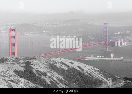 Cargo ship crossing the Golden Gate Bridge. - Stock Photo