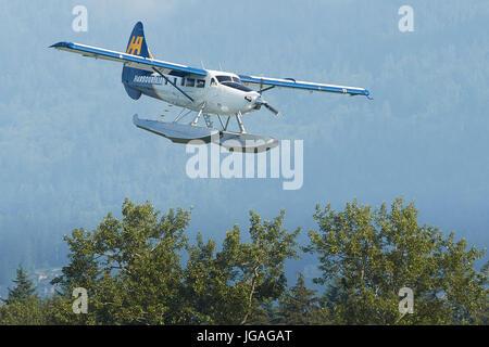 Harbour Air Seaplanes de Havilland Canada DHC-3-T Turbo Otter Floatplane Flying Low Over Woodlands In  British Columbia, Canada.