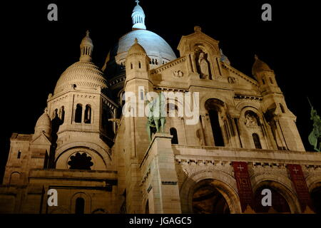 The Sacre Couer Basilica at the top of the Butte Montmartre in Paris shot at night - Stock Photo