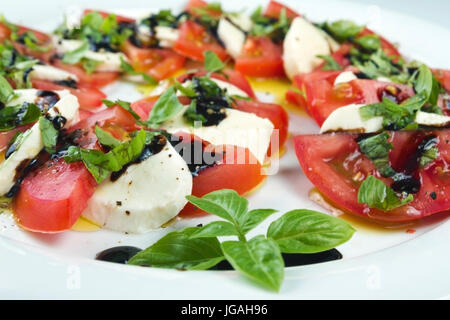 Caprese salad. Sliced tomatoes, mozzarella and shredded basil, poured with oil and vinegar, sprinkled with salt - Stock Photo