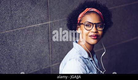 Confident young African woman wearing glasses and a bandana deep in thought while listening to music on earphones - Stock Photo