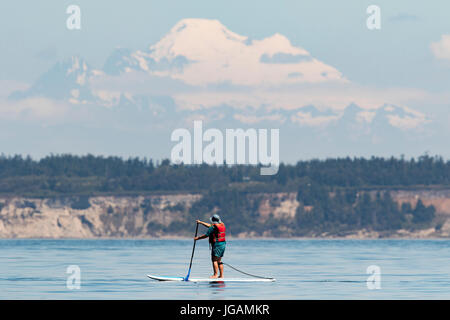 Stand up paddle boarding on Puget Sound with Mount Baker in background. - Stock Photo