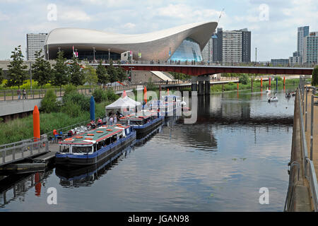 River Lea flowing through the Queen Elizabeth Olympic Park past the London Aquatics Centre in Stratford, Newham - Stock Photo