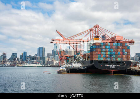 Ocean Going Container Ship Loading with Gantry Crane and Refueling in Port of Seattle with Skyline in Background - Stock Photo