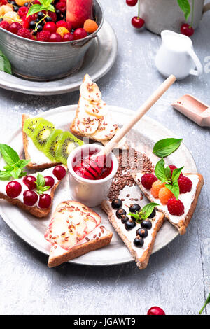 Fruit toast on grey background. Healthy breakfast. Clean eating. Dieting concept. Grain bread slices with cream - Stock Photo