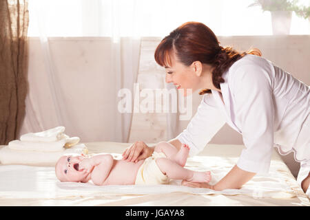 the little boy baby doctor doing massage hands and legs and back - Stock Photo