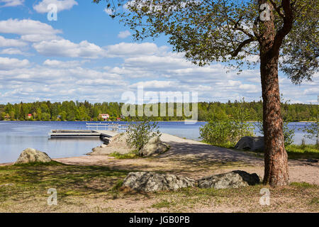 Sunny summer day and a lake in Finland. Empty swimming pier on the shore. - Stock Photo