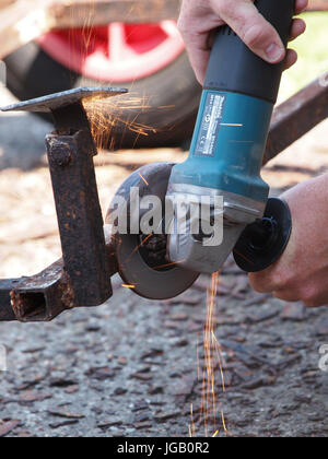 Close up view of an angle grinder being used on a rusty trailer. - Stock Photo