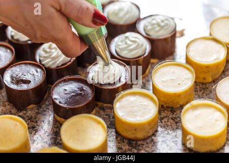 The pastry chef is decorating a mini cake with a whipped cream - Stock Photo