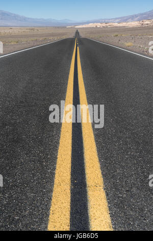 Long straight road in the desert of Death Valley, California - Stock Photo