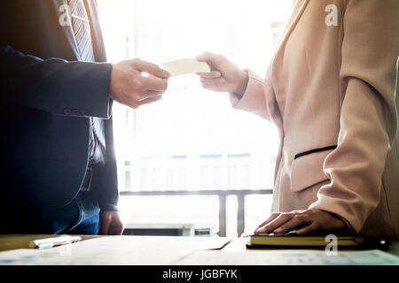 Closeup portrait of two successful business executive exchanging business card after meeting . - Stock Photo