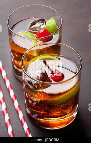 Cuba libre cocktail glasses on stone table - Stock Photo