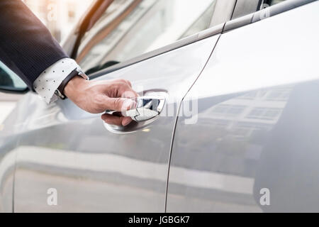 Chauffeur s hand on handle. Close-up of man in formal wear opening a passenger car door. - Stock Photo