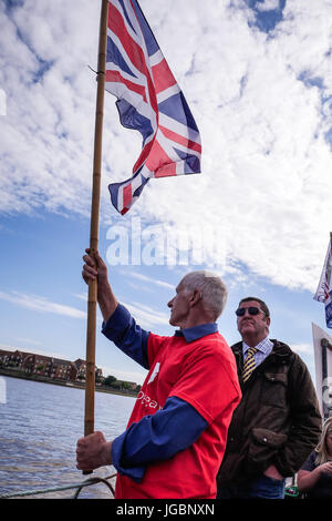A Vote Leave supporter with Mike Hookem MEP flying The Union Jack flag from a fishing boat during The EU Brexit - Stock Photo